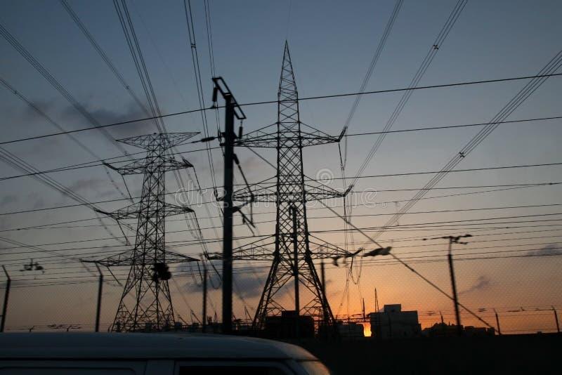 Elektriciteitspylonen en machtslijnen, bij zonsondergang stock foto's