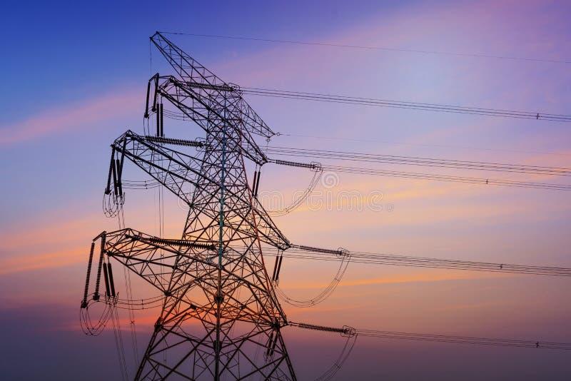 Elektriciteitspylonen, machtslijnen en bomen tegen een bewolkte hemel worden gesilhouetteerd die stock foto