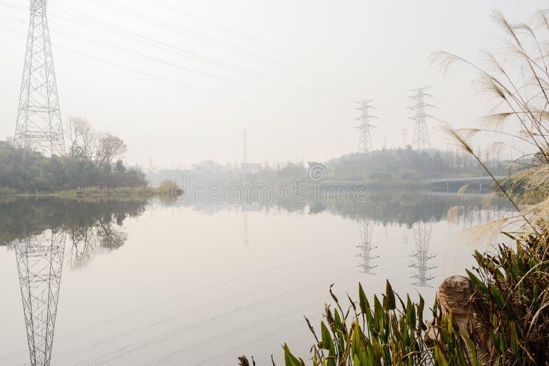 Elektriciteitspylonen met bezinningen in water op zonnige de winterdag royalty-vrije stock foto's