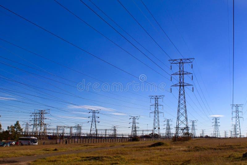 Elektriciteitspylonen tegen blauwe hemel op ruwe grond royalty-vrije stock foto