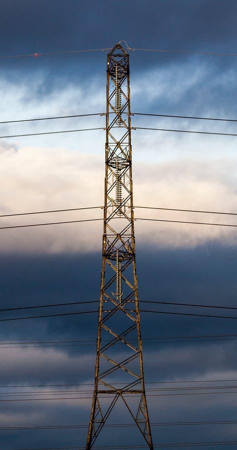 Elektriciteitspyloon en kabels tegen een stormachtige hemel royalty-vrije stock afbeeldingen