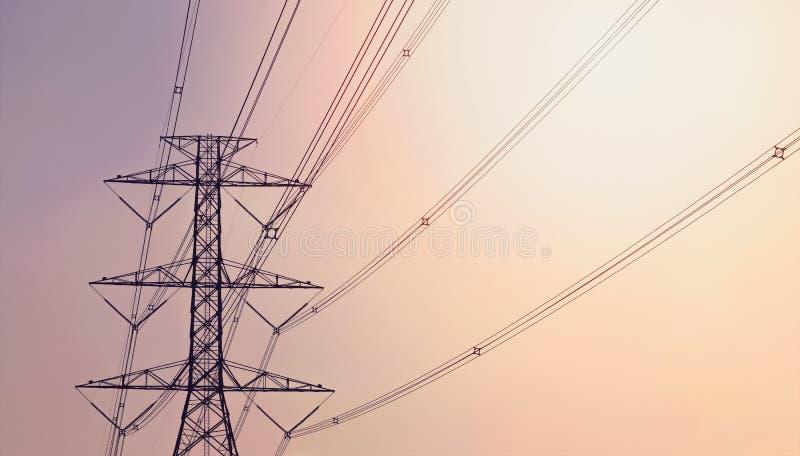 Elektriciteitspyloon tegen de violette en oranje achtergrond stock foto