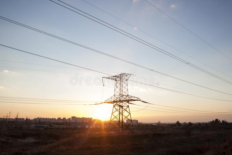 Elektriciteitspyloon tegen de zonsondergang stock foto's