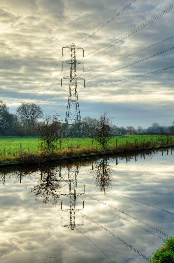 Elektriciteitspyloon in water wordt weerspiegeld dat stock fotografie