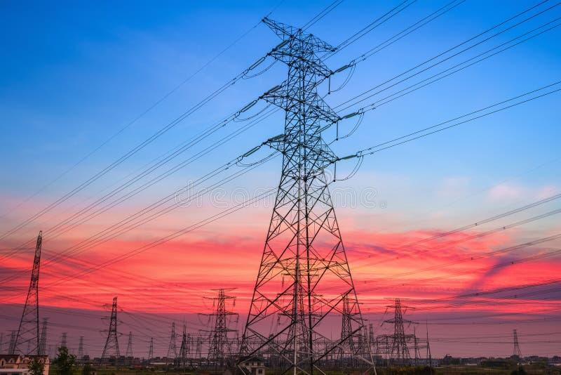 Elektriciteitspyloon in zonsondergang stock fotografie