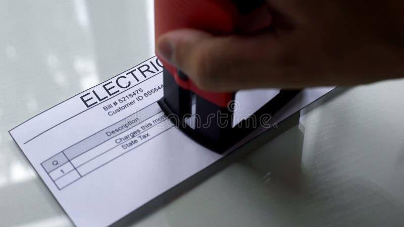 Elektriciteitsrekening, hand het stempelen verbinding op document, betaling voor de diensten, tarief royalty-vrije stock foto's