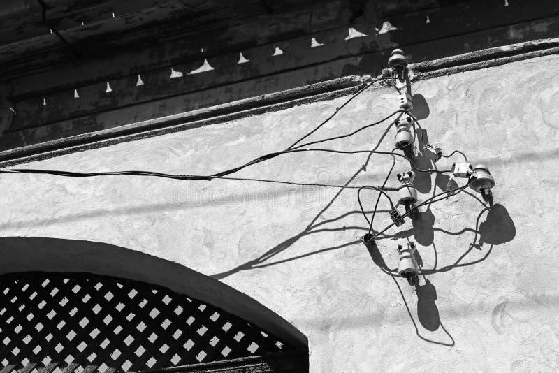Elektricitetskablar och telefonledningar på väggen arkivfoton