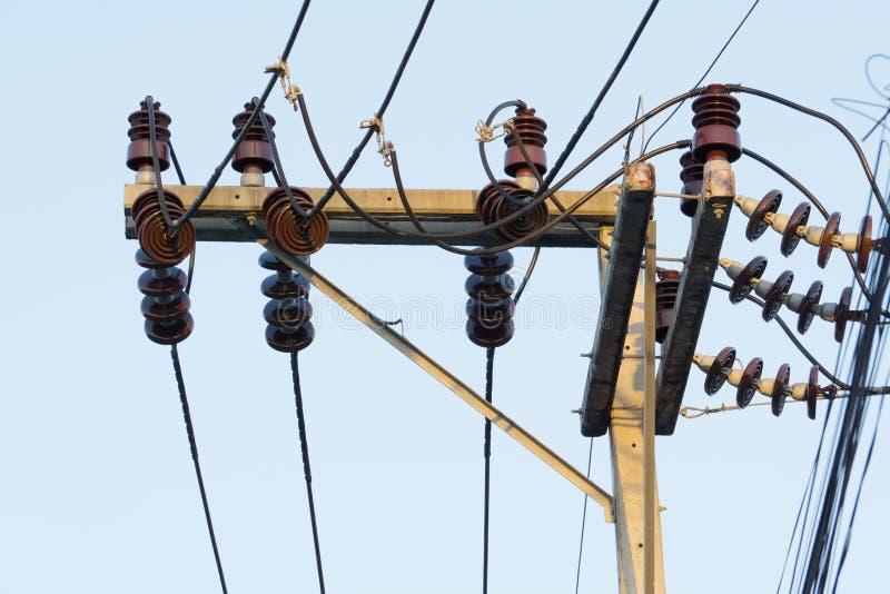 Elektricitetspoler och trådar förbinder till den höga spänningsmakttransformatorn arkivbilder