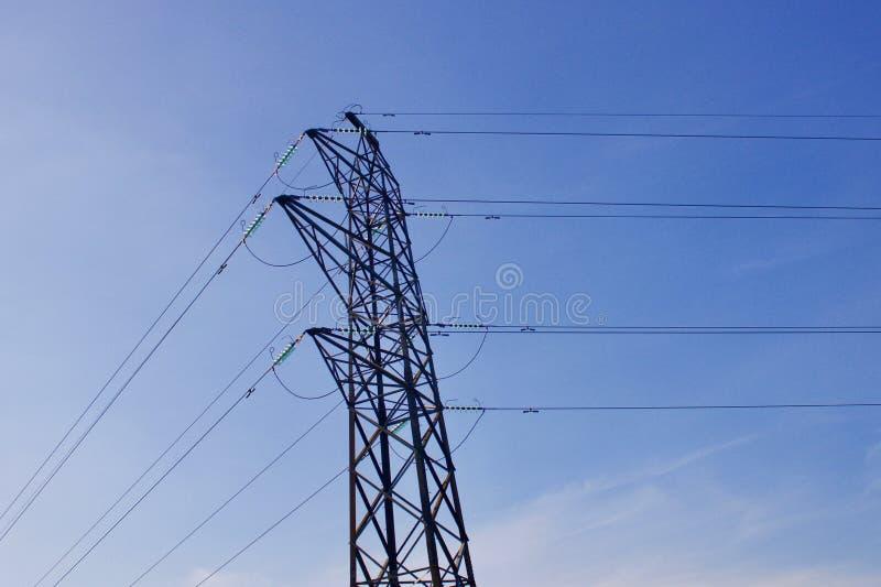 Elektricitetspylon med maktkablar mot bakgrund för blå himmel arkivfoto
