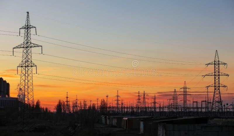 Elektricitetspyloner och kraftledningar på solnedgången arkivfoto