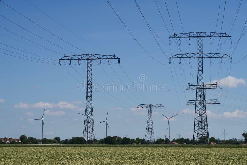 Elektricitetspyloner och vindturbiner royaltyfria bilder