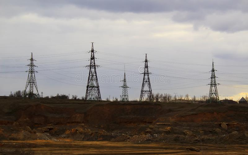Elektricitetsstationen, stänger sig upp höga spänningskraftledningar på solnedgången Elektricitetsfördelningsstation royaltyfri bild