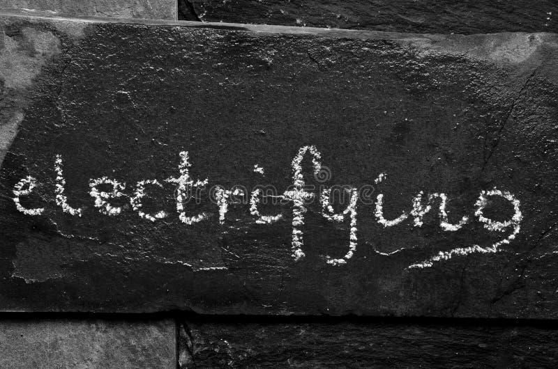 Elektrifiera för ord som är skriftligt med krita på den svarta stenen fotografering för bildbyråer