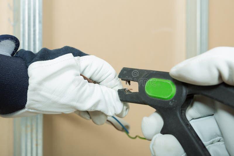 Elektriker bei der Arbeit - Installierung des Stromdrahtes in Gipskartonwand im Dachboden lizenzfreies stockfoto