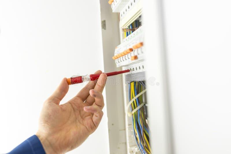 Elektriker, der eine elektrische Leiterplatte prüft stockfoto