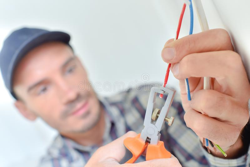 Elektriker, der einen Draht schnippelt lizenzfreies stockbild