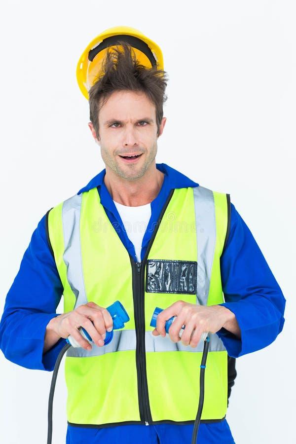 Elektriker, der einen Schock erhält, während das Halten verkabelt lizenzfreie stockbilder