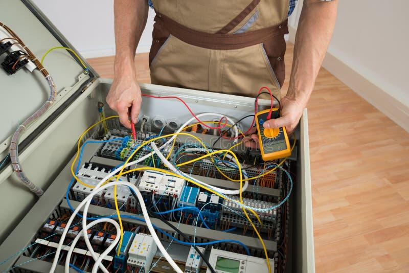 Elektriker, der einen Sicherungskasten überprüft stockfotografie