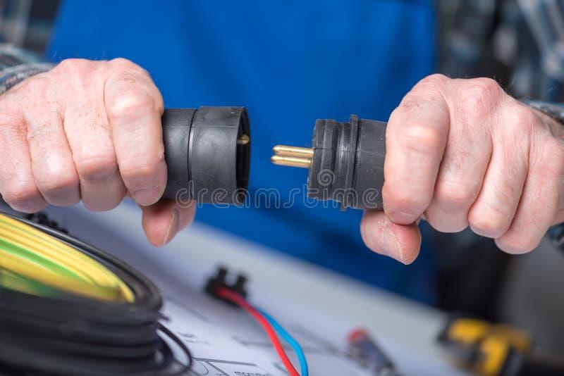 Elektriker, der elektrische Stecker hält lizenzfreie stockfotos