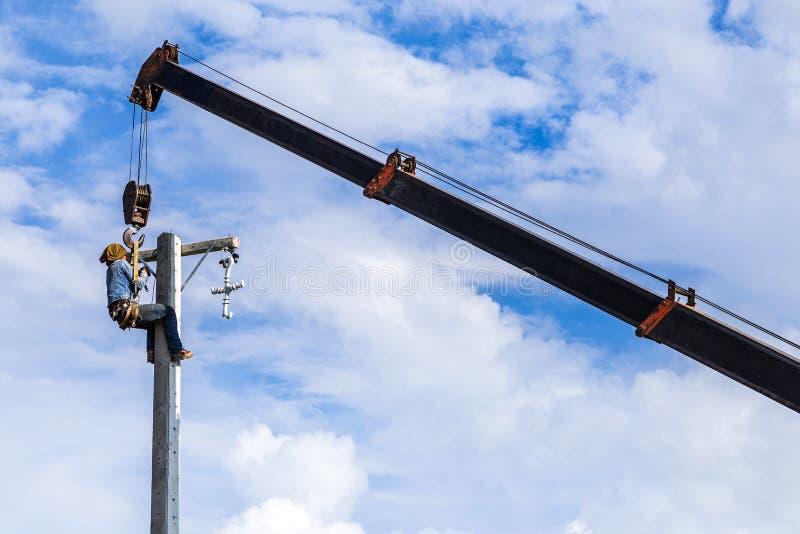 Elektriker, der an elektrischem Strommast arbeitet stockbild