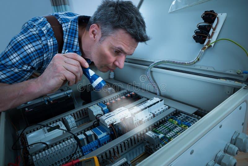 Elektriker, der fusebox mit Fackel analysiert lizenzfreie stockfotos