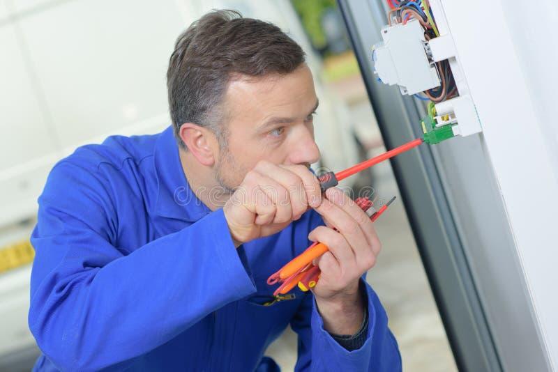 Elektriker, der herum am fusebox stößt stockbilder