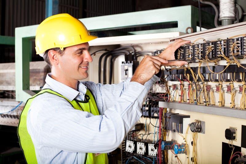 Elektriker, der industrielle Maschine repariert stockbild
