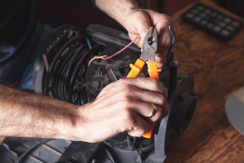 Elektriker, der Kabel mit Schneidern schneidet stockfotografie
