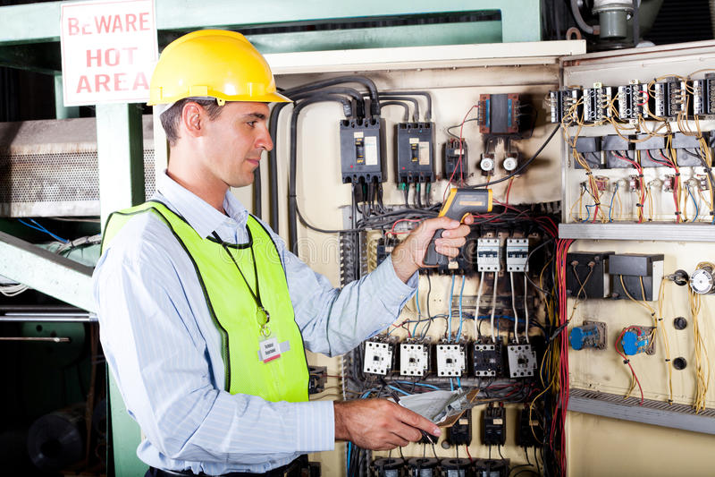 Elektriker, der Maschinentemperatur überprüft lizenzfreies stockbild