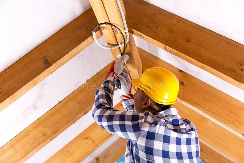 Elektriker, der mit Drähten am Dachbodenerneuerungsstandort arbeitet lizenzfreie stockfotos