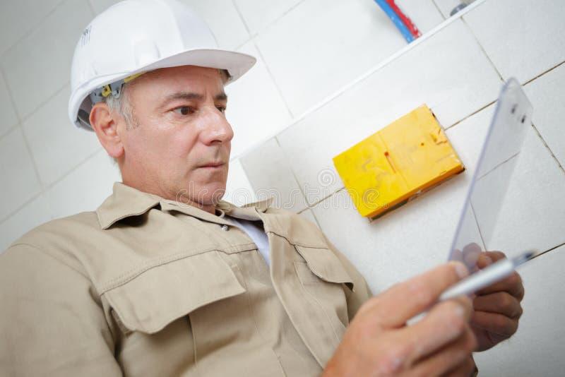 Elektriker, der in mit Ziegeln gedecktem Raum arbeitet lizenzfreies stockfoto