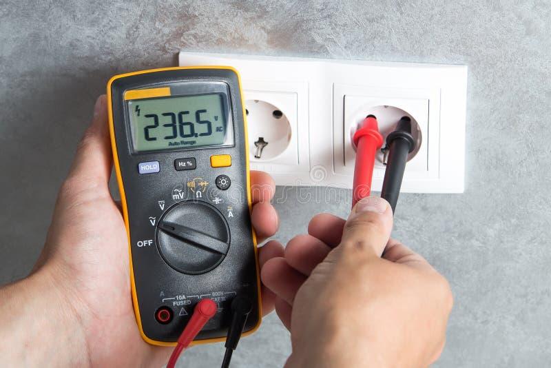 Elektriker, der Spannung im Sockel überprüft lizenzfreies stockfoto