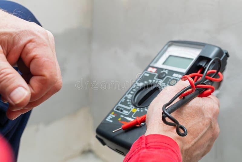 Elektriker, der Voltmeter verwendet lizenzfreie stockfotografie