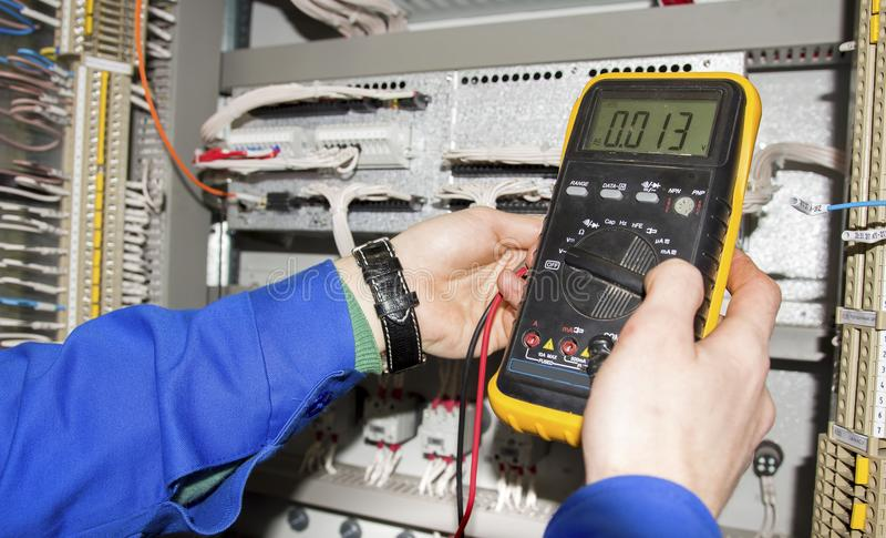 Elektriker misst Spannung durch Prüfvorrichtung Vielfachmessgerät ist in den Händen des Ingenieurs im elektrischen Kabinett stockbild