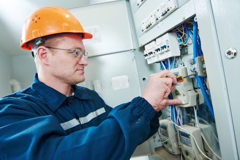 Elektriker mit Schraubenzieherreparatur-Schaltungsstellglied im Sicherungskasten lizenzfreies stockbild