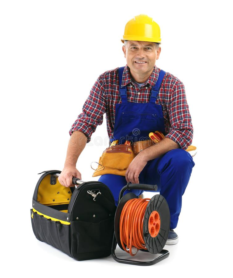 Elektriker mit Verlängerungskabelspule und Werkzeuge, die Uniform tragen lizenzfreies stockbild