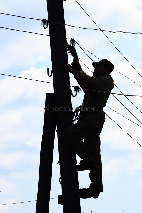 Elektriker på elkraftpol arkivfoto