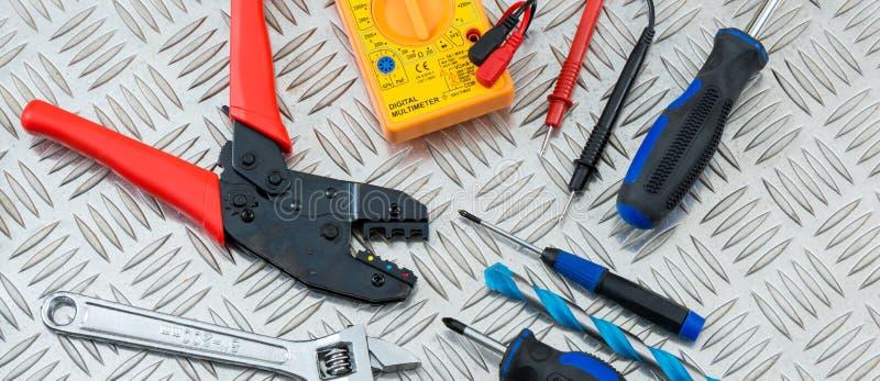 Elektriker ` s Werkzeuge auf einer Metallkreuzschraffieren-Platte lizenzfreie stockfotografie