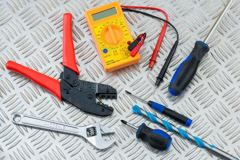 Elektriker ` s Werkzeuge und Ausrüstung auf Stahlschritt-Platte lizenzfreie stockfotografie