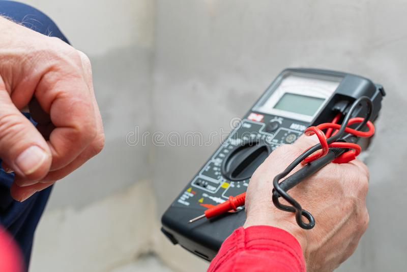 Elektriker som använder voltmetern royaltyfri fotografi