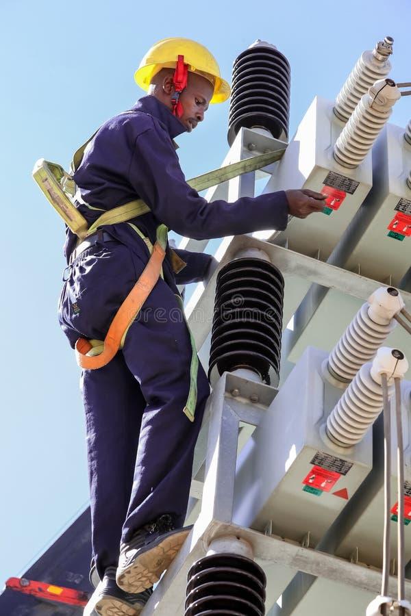 Elektriker som arbetar på höga spänningskraftledningar fotografering för bildbyråer