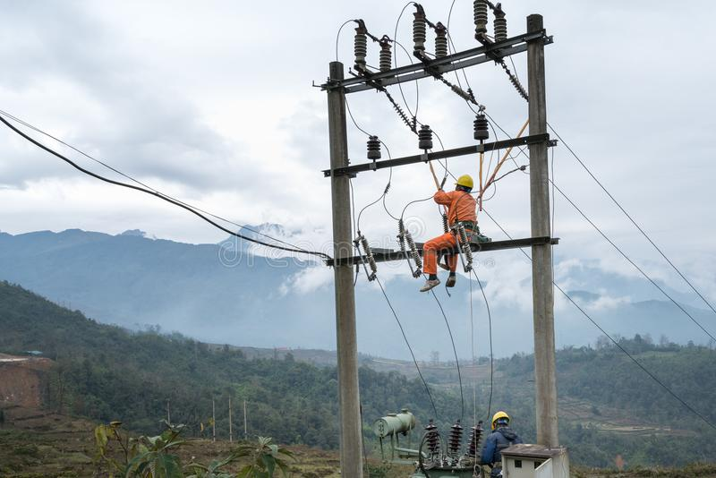 Elektriker som högt arbetar på elektricitetspol i Vietnam arkivfoton