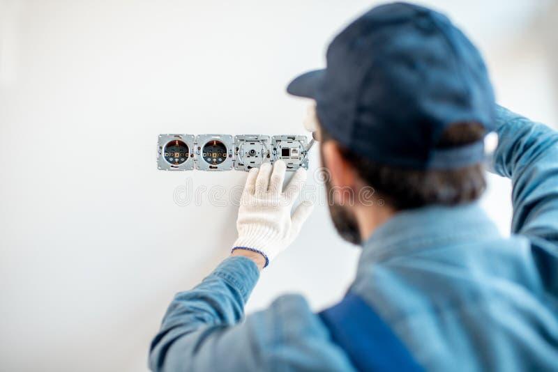 Elektriker som inomhus monterar håligheter royaltyfri fotografi