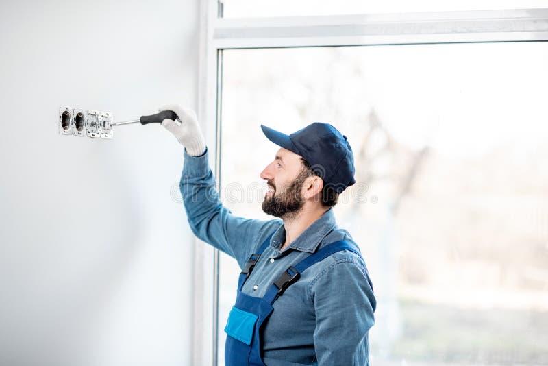 Elektriker som inomhus monterar håligheter royaltyfri bild