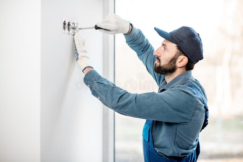 Elektriker som inomhus monterar håligheter royaltyfri foto