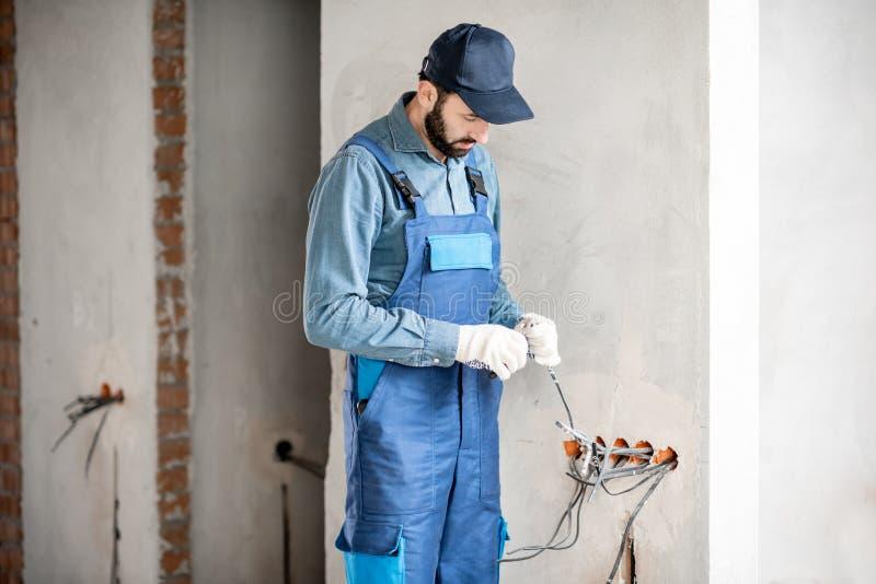 Elektriker som inomhus monterar ledningsnät royaltyfri foto
