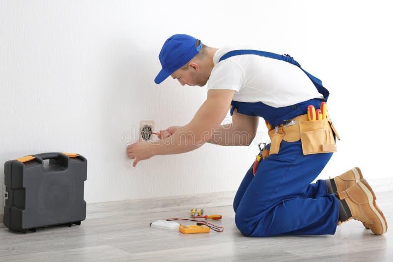Elektriker som inomhus reparerar håligheten royaltyfri bild