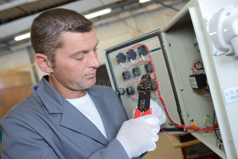 Elektriker som installerar den elektriska panelen arkivbilder