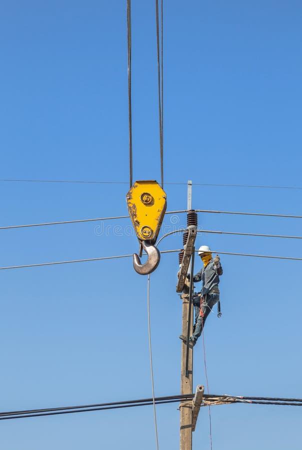Elektriker som klättrar arbete i höjden på konkret elkraftpol med den gula stora kranen royaltyfri bild