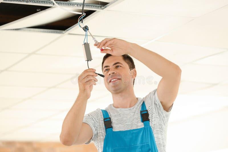 Elektriker som kontrollerar spänning på tak i ny lägenhet royaltyfri bild